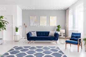 offener raum wohnzimmer interieur mit einem dunkelblauen sofa und ein sessel teppich auf dem boden und grafische dekorationen an der wand echtes foto