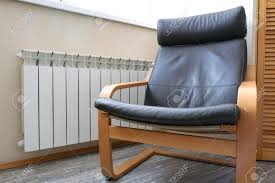 Modern Rocking Chair At The Radiator. Brown Leather Pillows... The Diwani Chair Modern Wooden Rocking By Ae Faux Wood Patio Midcentury Muted Blue Upholstered Mnwoodandleatherrockingchair290118202 Natural White Oak Outdoor Rockingchair Isolated On White Rock And Your Bowels Design With Thick Seat Rocking Chair Wooden Rocker Rinomaza Design Glossy Leather For Easy Life My Aashis
