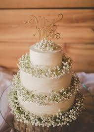 A White Cake Decorated With Babys Breath And Wooden Topper