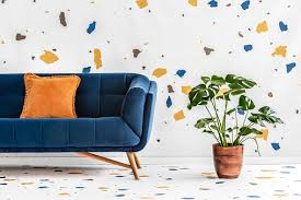 green monstera plant next to a blue sofa with an orange pillow