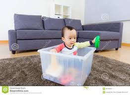 asiatisches baby das spielzeug am wohnzimmer spielt