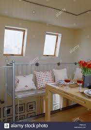 Cushions On Metal Bench In Attic Conversion Dining Room With Velux Windows And Pale Wood Table