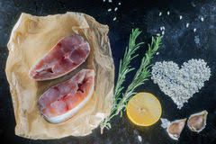 Fillet Of Raw Fish And Ingredients For Cooking On A Dark Background Stock Photo