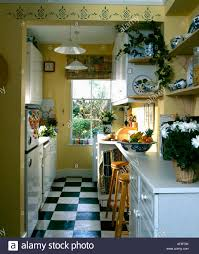 black and white vinyl floor tiles in yellow galley kitchen with