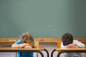aux bureaux élèves somnolents faisant une sieste aux bureaux dans la salle de