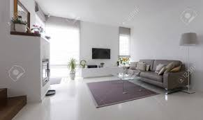 white living room with taupe leather sofa and glass table