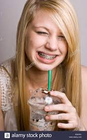 Teenage Girl Wincing From A Brain Freeze While Drinking Iced Coffee