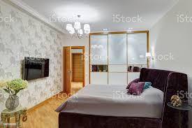 schlafzimmer mit kleiderschrank mit spiegel bett mit kopfteil velours und kissen und fernseher an der wand zimmer in grau violett weiß farben und
