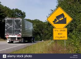 Semi Truck Drives Past A Road Sign Warning Drivers Of Steep Hill 9 ... Tow Truck Sign Stock Vector Jazzia 1036163 Truck Crossing Sign Mutcd W86 Us Signs And Safety Filejapanese Road Tractor Lane Asvg Wikimedia Commons Traffic Fork Lift Image I1441700 At Featurepics Christmas With Tree Set Delivery Yellow Road Street Royalty Free Sign Truck Xing Sym X48 Acm Bo Dg National Capital Industries Register To Join Chevy Legends Chevrolet Shop The Hillman Group 8in X 12in Caution Watch