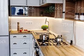 kochen auf moderne küche mit stahl ofen töpfe messer auf holzbrett mit gemüse pfeffer gewürze öl auf holz tischplatte zu hause essen stilvolle
