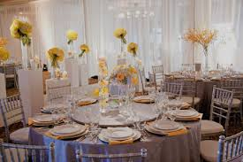 Silver And Yellow Wedding Decorations With Round Tables Wooden Chairs Also Glass Stand Vase