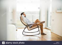 Young Man Sitting On Rocking Chair Relaxing Stock Photo: 282381651 ... Rocking Chair On The Wooden Floor 3d Rendering Thonet Chair At Puckhaber Decorative Antiques Man Sitting Rocking In His Living Room Looking Through Costway Classic White Wooden Children Kids Slat Back Fniture Oak Creating A Childrens From An Old Highchair 6 Steps Asta Recline Comfy Recliner Mocka Au Happy Pregnancy Sitting On Stock Image Of Jackson Rocker Click Black New Price Vintage Hitchcock