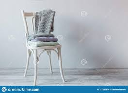 Stack Of Cozy Knitted Clothes On A Wooden Chair. Vintage ...