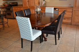Oval Trestle Dining Table With Parsons Chair Slipcovers And Tile Floors