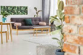 holzbank vor dunklen sofa mit kissen gegen eine wand mit blättern poster in gemütlichen wohnzimmer interieur mit pflanzen