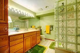 grünes badezimmer mit braunen schränke fliesen grün weichen teppich zimmer mit grünen und gelben handtücher kerzen