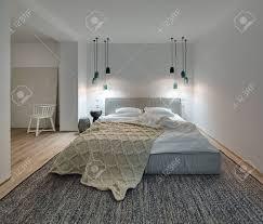 schlafzimmer in einem modernen stil mit weißen wänden und einem parkett mit einem teppich auf dem boden es gibt ein bett mit einem weißen kissen und