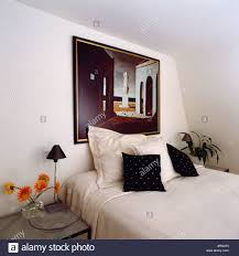 Modern Painting Above Bed With White Linen And Black Cushions In Attic Bedroom
