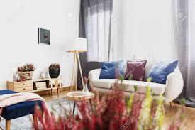 weiße le neben sofa mit blauen kissen unter einem fenster im wohnzimmer interieur