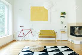 gelbes sofa zwischen rotem fahrrad und weißem regal im gemütlichen wohnzimmer mit kamin und puff auf teppich