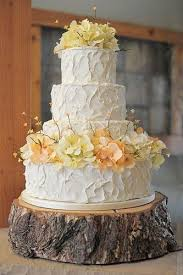 White Pale Yellow And Peach Wedding Cake On A Rustic Wood Slab Stand