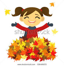 Girl playing in a pile of autumn leaves