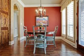 Minimalist Dining Room Design With Round Shape Wooden Table And Red Wall Color Also Laminated Floor Decorating Idea