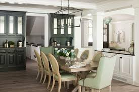 Charming Green And Brown Cottage Dining Room Is Illuminated By A Darlana Linear Lantern Hung Over Wood Trestle Table Seating Wingback Head