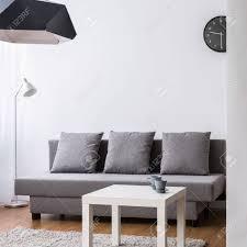 moderne wohnzimmer mit großen grauen sofa und kleinen couchtisch helle interieur mit dekorativen tapete
