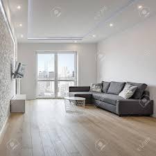 weißer wohnzimmer mit grauem sofa und backsteinmauer