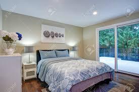 schlafzimmer im zweiten stock mit taupefarbenen wänden blauem bett und eigener terrasse