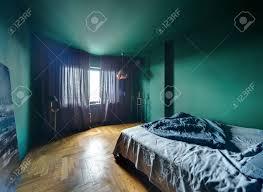 schlafzimmer in einem modernen stil mit türkisfarbenen wänden und parkett auf dem boden es gibt ein bett mit blauem kissen und decke blaues bild