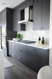 Modern Gray Kitchen Features Dark Flat Front Cabinets Paired With White Quartz Countertops And A