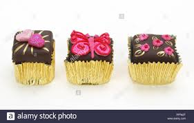 Small Chocolate Cakes With Pink Icing In Gold Cake Cases
