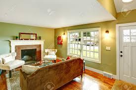 erfrischende wohnzimmer mit hellgrünen wänden parkettboden und weiße decke mit braunen sofa weiße stühle und couchtisch aus glas ausgestattet mit