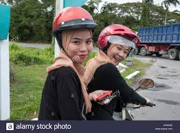 Two Identically Dressed Muslim Girls Sit On A Motor Scooter In Mukah Division