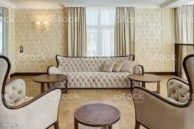 blick auf stilvolle und helle wohnzimmer mit großen fenstern in den farben beige und braun klassisches interieur aus großen raum mit beige sofa zwei