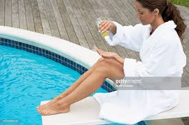 Young Woman On Diving Board Pouring Oil Into Hand Side View Stock Photo