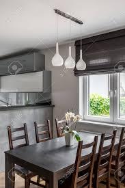 solide esstisch stühle aus holz hängende le und dekorative fensterrollo offene küche im hintergrund