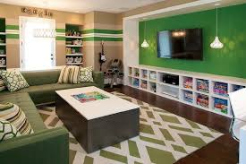 Green Family Room Features A Accent Wall Lined With Flatscreen TV Flanked By Pendants
