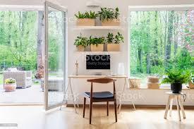 zenhomeoffice mit computer in einem schönen geräumigen wohnzimmer interieur mit pflanzen und eine außenansicht durch große fenster stockfoto und mehr