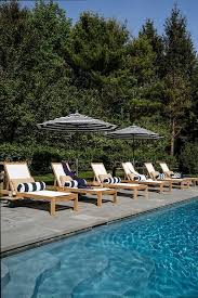 Outdoor Pool Deck Designed With Teak Loungers On Slate Tiles Accented Navy Blue Striped Bolster Pillows Under Matching Lounger Umbrellas