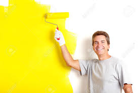 Smiling Handsome Man Painting Interior Wall Of Home Stock Photo
