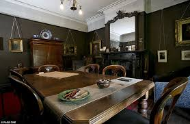 The Dining Room Has Dark Painted Walls Gilt Framed Oil Paintings Hanging From A