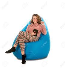 lächelnde junge frau die auf blauem sitzsack für wohnzimmer oder anderen raum sitzt und eine tablette lokalisiert auf weißem hintergrund hält