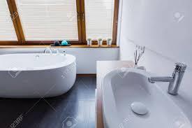 moderne badezimmer mit weißen wänden dunklen fliesen auf dem boden schneeweißen badewanne waschbecken und fenster