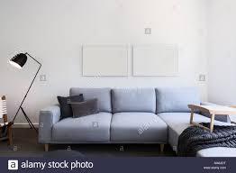 hellblau bettwäsche sofa und leere bilder in ein wohnzimmer