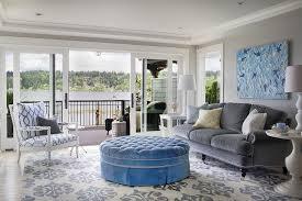 Gray Velvet Roll Arm Sofa On Caster Legs With A Blue Tufted Ottoman