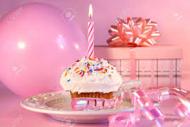 Little cupcake with candle balloon and t on pink background Stock