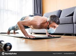 selective focus of shirtless in mask doing press ups on fitness mat in living room 367923712